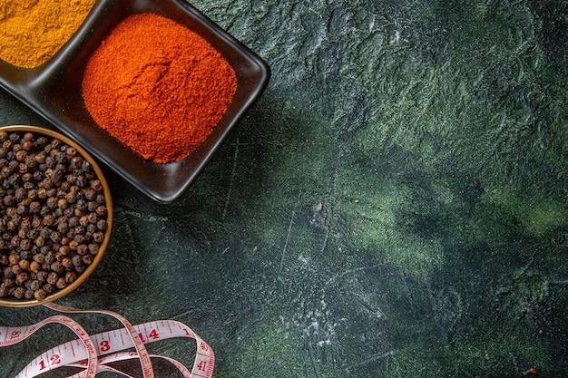 Vue de dessus des bols d'épices remplis de poivron rouge et de gingembre jaune mètre sur la surface des couleurs de mélange