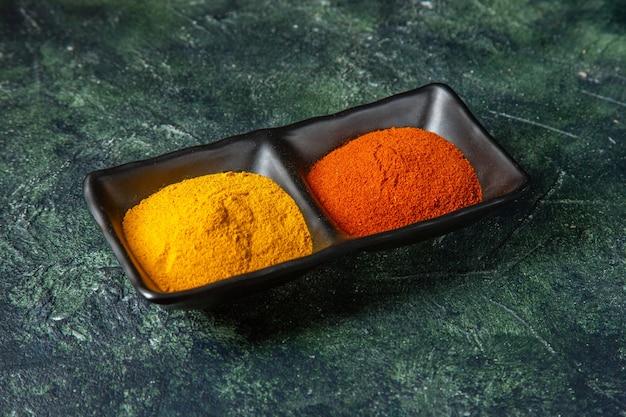 Vue de dessus des bols à épices remplis de poivron rouge et de gingembre jaune sur la surface des couleurs mixtes avec espace libre