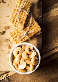 Vue de dessus de bols de noix de cajou avec barre d'énergie de sésame sur planche à découper