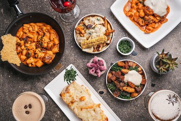 Vue de dessus des bols de pâtes cuites avec des salades et des légumes frits sur la table
