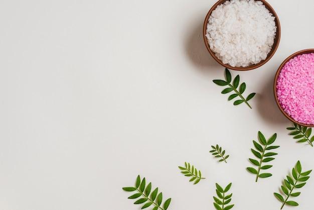 Une vue de dessus de bols de sel roses et blancs avec des feuilles vertes sur fond blanc