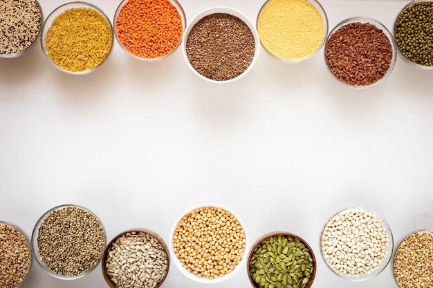 Vue de dessus des bols en verre avec des céréales, des haricots et des graines sur fond blanc avec copie espace au milieu.