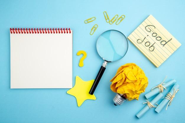 Vue de dessus bon travail écrit sur papier à lettres faites défiler les notes autocollantes lupa idée ampoule concept ordinateur portable sur fond bleu