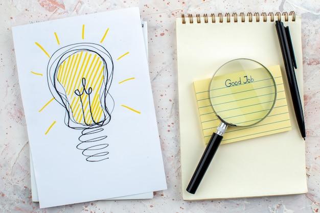 Vue de dessus bon travail écrit sur pense-bête cahier stylo lupa idée ampoule dessin sur papier sur table