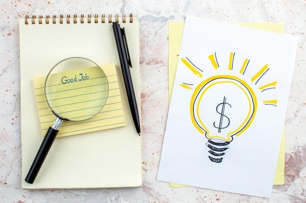 Vue de dessus bon travail écrit sur pense-bête cahier stylo lupa idée d'entreprise ampoule dessin sur papier sur table