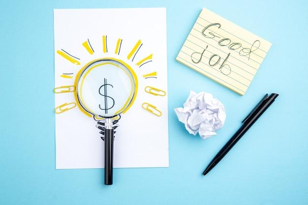 Vue de dessus bon travail écrit sur pense-bête lupa sur papier avec business idealight bulb photo stylo noir sur fond bleu