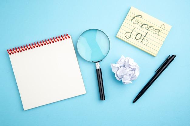 Vue de dessus bon travail écrit sur pense-bête stylo noir lupa cahier sur fond bleu