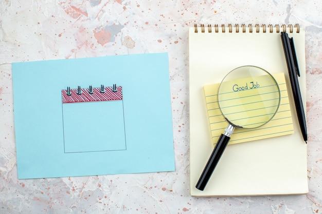 Vue de dessus bon travail écrit sur sticky note cahier stylo papier bleu lupa