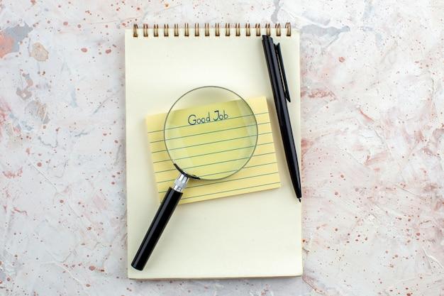 Vue de dessus bon travail écrit sur sticky note pen lupa sur ordinateur portable sur table espace libre