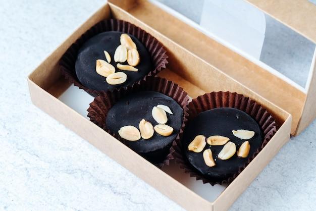 Vue de dessus des bonbons au chocolat avec des arachides dans une boîte