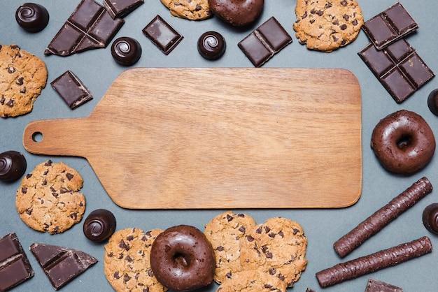 Vue de dessus des bonbons au chocolat autour d'une planche à découper