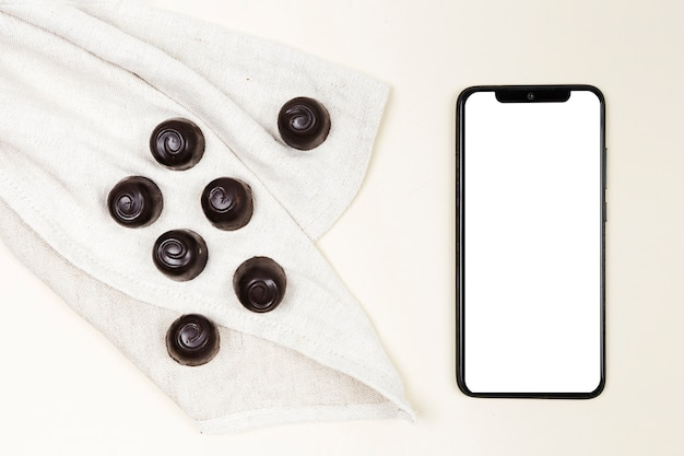 Vue de dessus des bonbons au chocolat avec smartphone