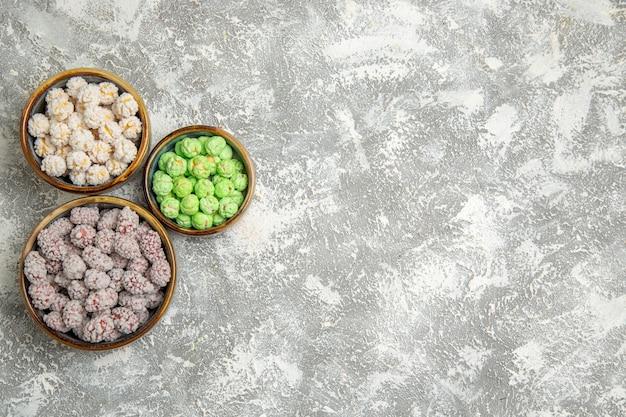 Vue de dessus des bonbons au sucre à l'intérieur de petites assiettes sur fond blanc
