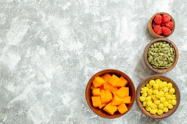 Vue de dessus des bonbons et de la citrouille avec des graines sur fond blanc sucre de couleur bonbon