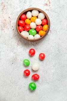 Vue de dessus des bonbons colorés sur un arc-en-ciel de sucre de couleur de bureau blanc