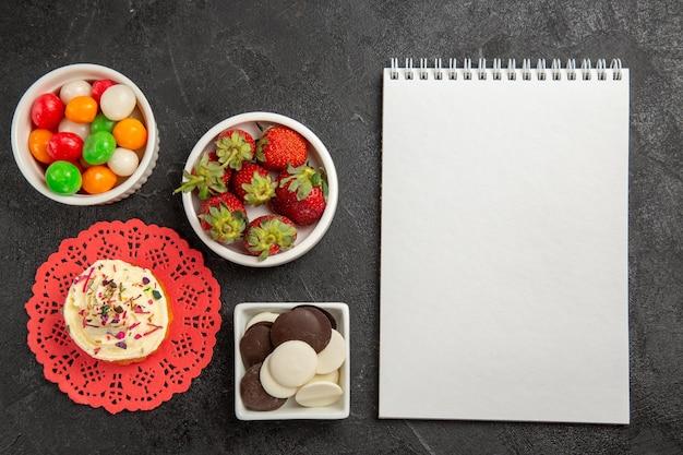 Vue de dessus des bonbons colorés avec des biscuits et des fraises sur fond sombre