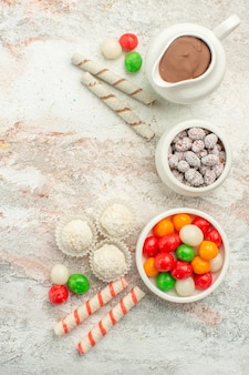 Vue de dessus des bonbons colorés avec des biscuits sur un gâteau au thé aux biscuits arc-en-ciel de couleur de bureau blanc