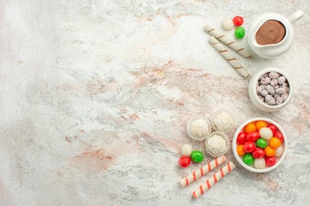 Vue de dessus des bonbons colorés avec des biscuits sur le gâteau de thé aux biscuits arc-en-ciel de couleur de fond blanc clair