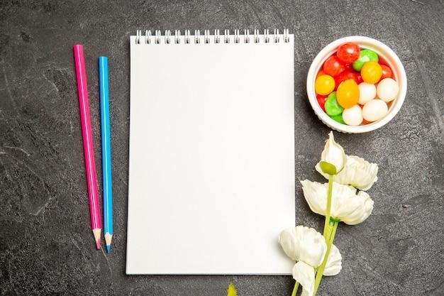 Vue de dessus des bonbons colorés avec bloc-notes et crayons sur un espace gris