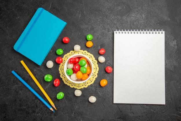 Vue de dessus des bonbons colorés avec bloc-notes sur des fruits sucrés arc-en-ciel de couleur de surface sombre