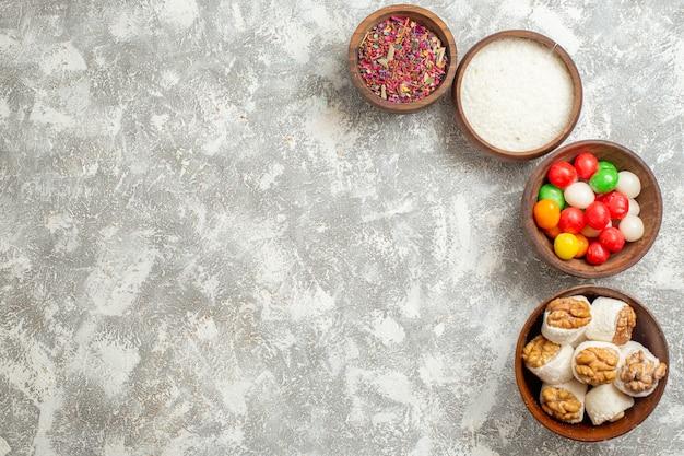 Vue de dessus des bonbons colorés avec des confitures de noix sur l'arc-en-ciel de bonbons couleur table blanche