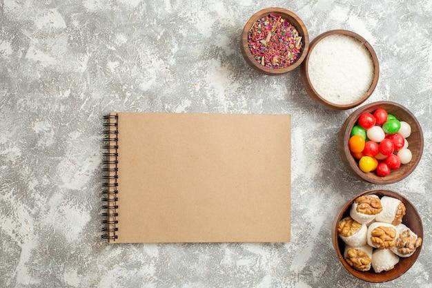 Vue de dessus des bonbons colorés avec des confitures de noix sur le sucre d'arc-en-ciel de couleur de bonbons de table blanche