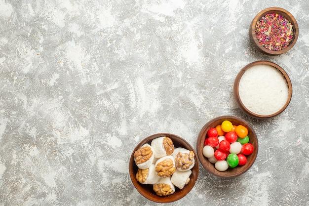 Vue de dessus des bonbons colorés avec des confitures de noix sur la table blanche couleur arc-en-ciel bonbons noix