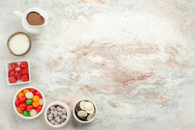 Vue de dessus des bonbons colorés avec des cookies sur un biscuit de bonbons arc-en-ciel de couleur de fond blanc