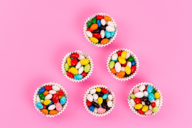 Une vue de dessus des bonbons colorés à l'intérieur des paquets de papier sur rose