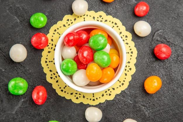 Vue de dessus des bonbons colorés sur le thé sucré arc-en-ciel de couleur de surface sombre