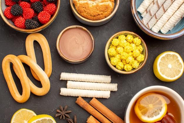 Vue de dessus des bonbons à la confiture avec une tasse de thé et des biscuits sur une surface sombre thé aux biscuits aux bonbons sucrés