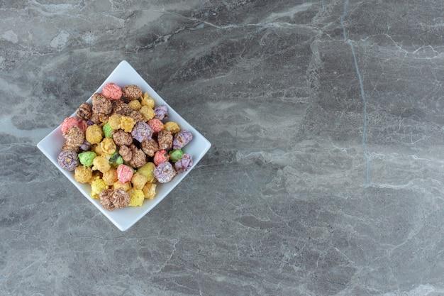 Vue de dessus des bonbons faits maison frais dans un bol en céramique blanche.