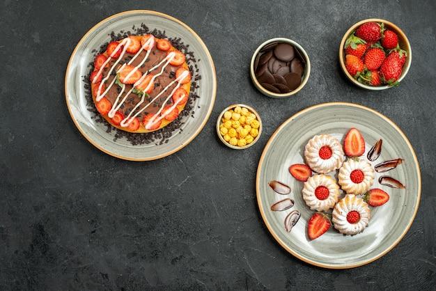 Vue de dessus des bonbons et des gâteaux, des gâteaux et des biscuits appétissants à côté de bols de chocolat aux noisettes aux fraises sur une table sombre