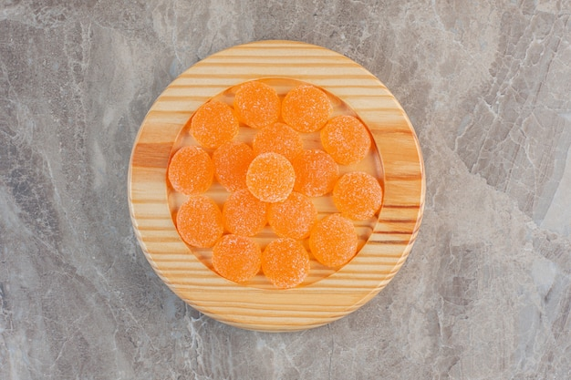 Vue de dessus des bonbons à la gelée d'orange sur planche de bois.