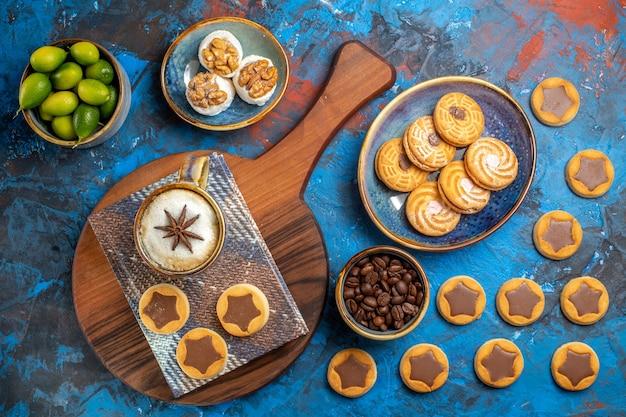 Vue de dessus de bonbons de loin une tasse de nappe de café sur le conseil des biscuits aux agrumes