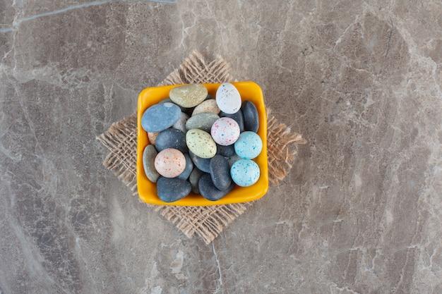 Vue de dessus des bonbons en pierre dans un bol orange.