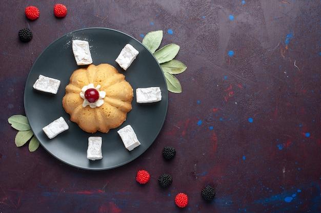 Vue de dessus des bonbons en poudre de sucre délicieux nougat avec des baies de gâteau et de confiture sur une surface sombre