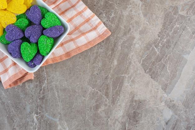 Vue de dessus des bonbons de la saint-valentin en forme de coeur à l'intérieur d'un bol sur une serviette.