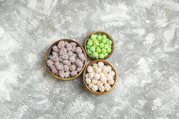 Vue de dessus des bonbons de sucre à l'intérieur de petites assiettes sur le fond blanc bonbon sucre bonbon thé biscuit sucré