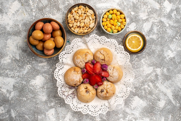 Vue de dessus des bonbons sucrés avec des biscuits aux noix sur une surface blanche