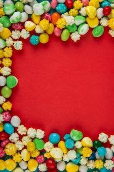 Vue de dessus des bonbons sucrés colorés sur fond rouge avec copie espace