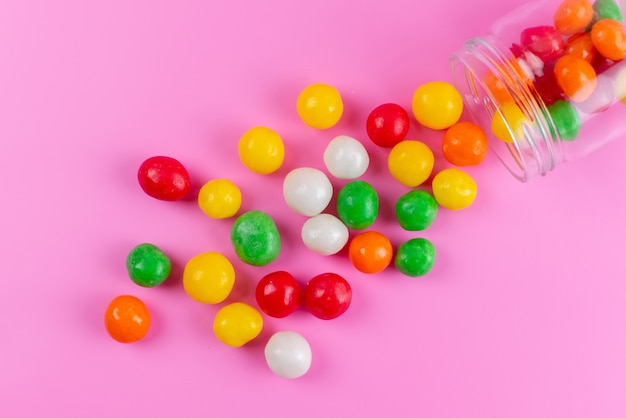 Une vue de dessus des bonbons sucrés colorés à l'intérieur et à l'extérieur peuvent sur rose, couleur sucrée de sucre
