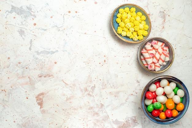 Vue de dessus des bonbons sucrés avec des confitures sur la table blanche de bonbons de sucre de couleur arc-en-ciel