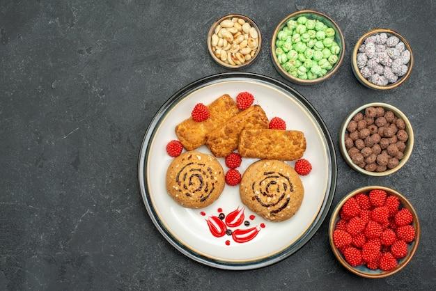 Vue de dessus des bonbons sucrés délicieux biscuits sur fond gris bonbons gâteau au thé au sucre sucré