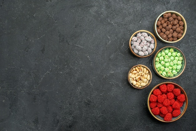 Vue de dessus des bonbons sucrés à l'intérieur de petits pots sur fond gris bonbons thé au sucre sucré