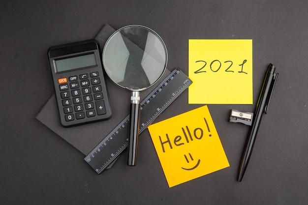 Vue de dessus bonjour et écrit sur des notes autocollantes règle de stylo lupa calculatrice bloc-notes taille-crayon sur noir