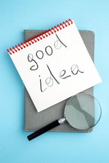 Vue de dessus bonne idée et cahier gris lupa sur fond bleu