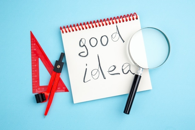 Vue de dessus bonne idée écrite sur cahier à spirale lupa dessin règle triangle compas sur fond bleu
