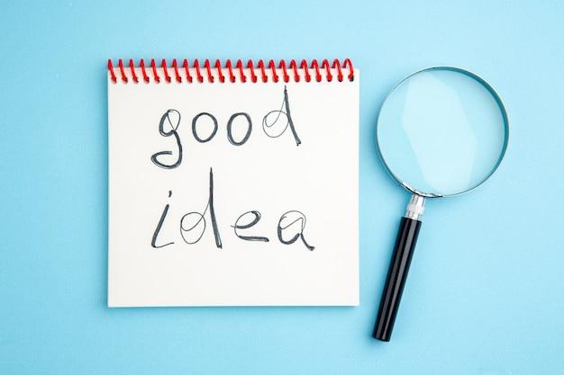 Vue de dessus bonne idée écrite sur cahier à spirale lupa sur fond bleu