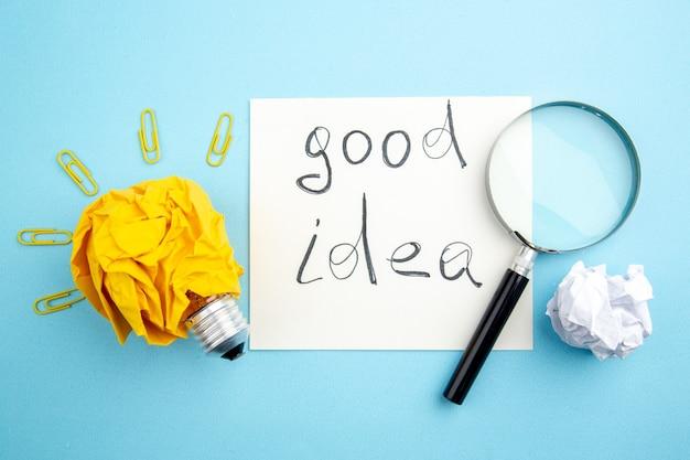 Vue de dessus bonne idée écrite sur papier concept d'ampoule idée lupa avec du papier froissé et des clips de gemme sur la table